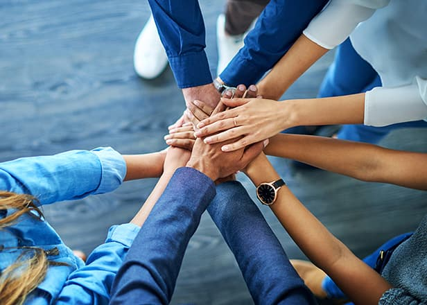 A group of people with hands together.